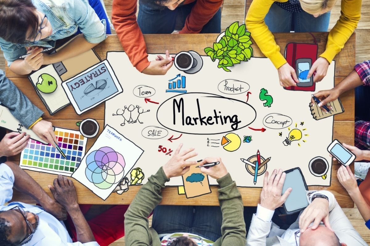 persone sedute a un tavolo con grafiche marketing per evoluzione couponing